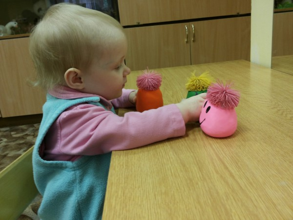 Kleines Mädchen spielt zärtlich mit kleinen lustigen Figuren
