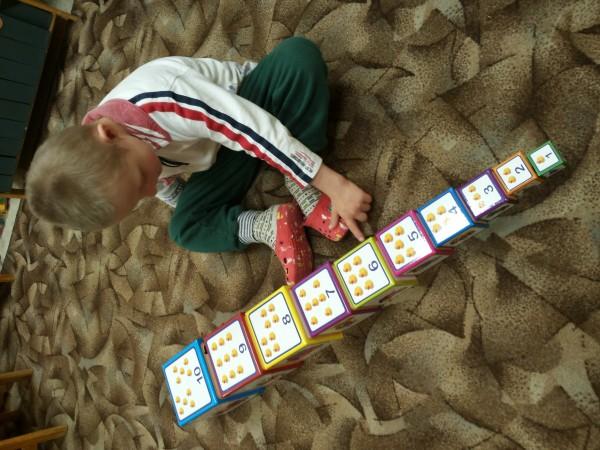 Ein Junge übt das Zählen mit einem Zahlenturm