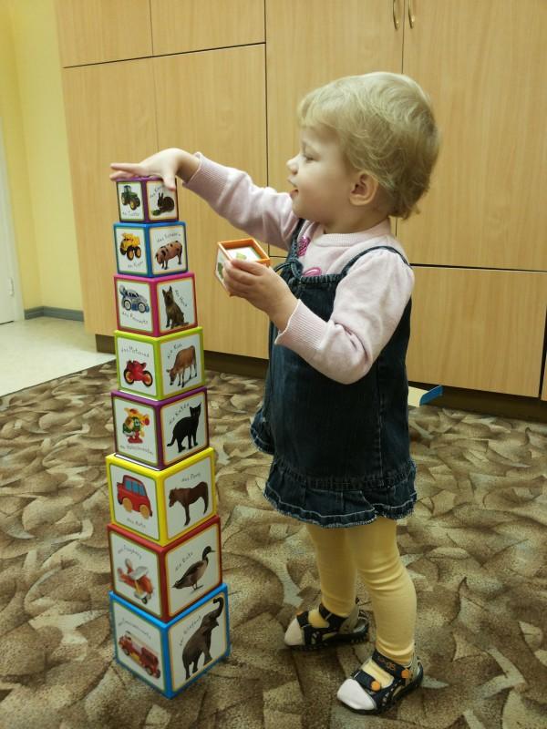 Ein kleines Mädchenbaut einen Turm so hoch wie sie selbst groß ist