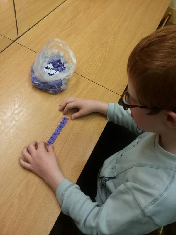 Ein Junge legt seinen Namen mit einem Buchstabenpuzzle