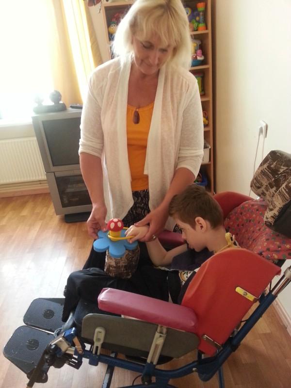 Eine Erzieherin führt die Hand von einem Rollstuhlkind